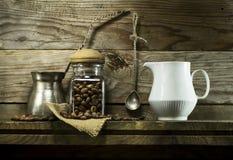 在玻璃瓶子和匙子的咖啡豆在架子 库存图片