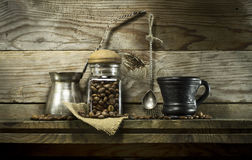在玻璃瓶子和匙子的咖啡豆在架子 免版税库存图片