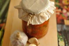在玻璃瓶子和大蒜的罐装菜 免版税库存图片