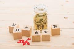 在玻璃瓶子和木立方体的美元钞票与捐赠字法 免版税库存图片