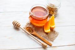 在玻璃瓶子和桔子的蜂蜜在木白色的背景 免版税库存图片