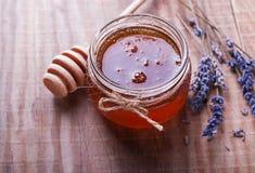 在玻璃瓶子和淡紫色的蜂蜜在木桌上开花 库存照片