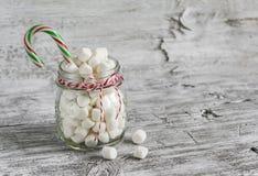 在玻璃瓶子和糖果-圣诞节礼物的蛋白软糖,轻的木表面上 库存图片