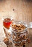 在玻璃瓶子和蜂蜜的自创健康格兰诺拉麦片 库存照片