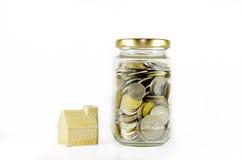 在玻璃瓶子旁边的微型房子用在白色背景隔绝的硬币填装了 库存照片
