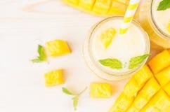 在玻璃瓶子有秸杆的,薄荷叶,芒果切片,关闭的新近地被混和的黄色芒果果子圆滑的人,顶视图 白色木 库存照片