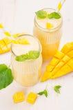 在玻璃瓶子有秸杆的,薄荷叶,芒果切片,关闭的新近地被混和的黄色芒果果子圆滑的人 软的白色木板 免版税库存照片