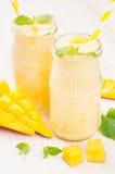 在玻璃瓶子有秸杆的,薄荷叶,芒果切片,关闭的新近地被混和的黄色芒果果子圆滑的人 库存照片