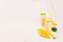 在玻璃瓶子有秸杆的,薄荷叶,芒果切片,拷贝空间的新近地被混和的黄色芒果果子圆滑的人 软的白色木蟒蛇 库存照片
