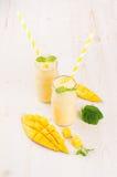 在玻璃瓶子有秸杆的,薄荷叶,芒果切片,拷贝空间的新近地被混和的黄色芒果果子圆滑的人 图库摄影
