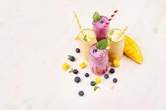 在玻璃瓶子有秸杆的,薄荷叶,芒果切片,莓果的新近地被混和的黄色和紫罗兰色果子圆滑的人 软的白木bo 免版税库存照片