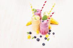 在玻璃瓶子有秸杆的,薄荷叶,芒果切片,莓果的新近地被混和的黄色和紫罗兰色果子圆滑的人 免版税库存图片