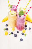 在玻璃瓶子有秸杆的,薄荷叶,芒果切片,莓果的黄色和紫罗兰色果子圆滑的人 库存照片