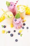 在玻璃瓶子有秸杆的,薄荷叶,芒果切片,莓果的黄色和紫罗兰色果子圆滑的人 免版税库存照片