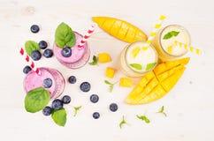 在玻璃瓶子有秸杆的,薄荷叶,芒果切片,莓果,顶视图的新近地被混和的黄色和紫罗兰色果子圆滑的人 库存图片