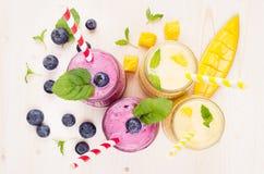 在玻璃瓶子有秸杆的,薄荷叶,芒果切片,莓果,顶视图的新近地被混和的黄色和紫罗兰色果子圆滑的人 图库摄影