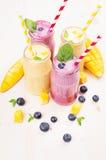 在玻璃瓶子有秸杆的,薄荷叶,芒果切片,蓝莓的新近地被混和的黄色和紫罗兰色果子圆滑的人 软的白色woode 图库摄影