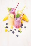 在玻璃瓶子有秸杆的,薄荷叶,芒果切片,蓝莓的新近地被混和的黄色和紫罗兰色果子圆滑的人 免版税库存图片