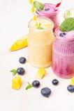 在玻璃瓶子有秸杆的,薄荷叶,芒果切片,蓝莓,关闭的新近地被混和的黄色和紫罗兰色果子圆滑的人 软的w 免版税库存图片