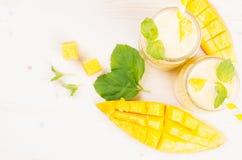 在玻璃瓶子有秸杆的,薄荷叶,芒果切片,顶视图的新近地被混和的黄色芒果果子圆滑的人 白色木板后面 免版税图库摄影