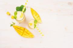 在玻璃瓶子有秸杆的,薄荷叶,芒果切片,顶视图的新近地被混和的黄色芒果果子圆滑的人 库存照片