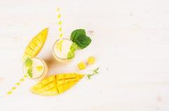 在玻璃瓶子有秸杆的,薄荷叶,芒果切片,顶视图的黄色芒果果子圆滑的人 白色木板背景,拷贝温泉 免版税库存图片