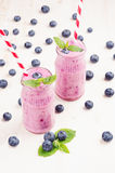 在玻璃瓶子有秸杆的,薄荷叶,莓果的新近地被混和的紫罗兰色蓝莓果子圆滑的人 白色木板背景 免版税库存图片