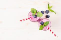在玻璃瓶子有秸杆的,薄荷叶,莓果,顶视图的新近地被混和的紫罗兰色蓝莓果子圆滑的人 白色木板backg 库存图片