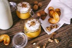在玻璃瓶子的南瓜奶昔用被鞭打的奶油、奶糖、核桃和蜂蜜曲奇饼 瓶牛奶 黑暗木 库存照片