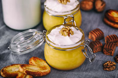 在玻璃瓶子的南瓜奶昔用被鞭打的奶油、奶糖、核桃和蜂蜜曲奇饼 瓶牛奶 灰色餐巾 免版税图库摄影