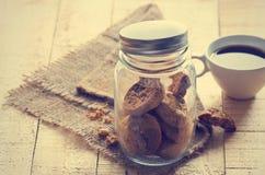 在玻璃瓶子的巧克力曲奇饼在大袋和咖啡在木 库存照片