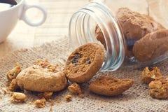 在玻璃瓶子的巧克力曲奇饼在大袋和咖啡在木 免版税图库摄影