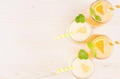 在玻璃瓶子的新近地被混和的橙色和黄色柠檬圆滑的人有秸杆的,薄荷的叶子,顶视图 白色木板背景,警察 图库摄影