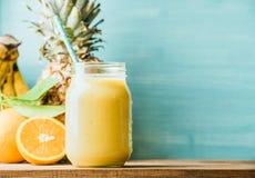 在玻璃瓶子的新近地被混和的黄色和橙色果子圆滑的人有秸杆的 免版税库存图片
