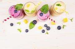 在玻璃瓶子的新近地被混和的黄色和紫罗兰色果子圆滑的人有秸杆、薄荷叶、芒果切片和莓果的,顶视图 软的wh 库存图片