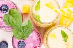 在玻璃瓶子的新近地被混和的黄色和紫罗兰色果子圆滑的人有秸杆、薄荷叶、芒果切片和莓果的,关闭,上面竞争 免版税库存图片