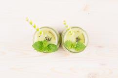 在玻璃瓶子的新近地被混和的绿色猕猴桃圆滑的人有秸杆的,薄荷的叶子,顶视图 库存图片