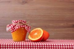 在玻璃瓶子的橙色果酱和在一张红色方格的桌布的橙色一半 木背景 库存图片