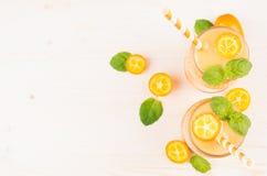 在玻璃瓶子的橙色柑橘金桔果子圆滑的人有秸杆的,薄荷的叶子,逗人喜爱的成熟莓果,顶视图 白色木板backgroun 库存照片