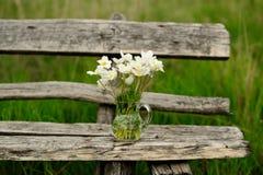 在玻璃瓶子的白色银莲花属在老木桌上 免版税库存图片