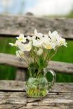 在玻璃瓶子的白色银莲花属在老木桌上 免版税库存照片