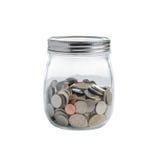 在玻璃瓶子的硬币在白色背景 免版税库存照片