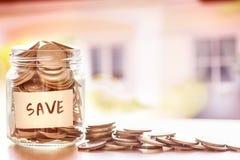 在玻璃瓶子的硬币有房子defocused背景,金钱savin 免版税库存图片