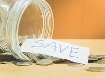 在玻璃瓶子的硬币金钱的保存财政概念 库存照片