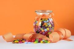 在玻璃瓶子的糖果在橙色和白色背景 图库摄影
