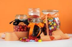 在玻璃瓶子的糖果对橙色墙壁 免版税库存图片