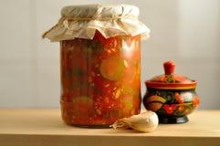 在玻璃瓶子的罐装菜在木委员会 库存照片
