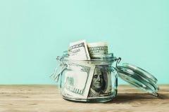 在玻璃瓶子的美金在木桌上 铸造概念保证金堆保护的节省额 免版税图库摄影