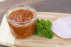 在玻璃瓶子的自创西红柿酱用鲜美火腿抽了整个和被切的特写镜头 库存图片