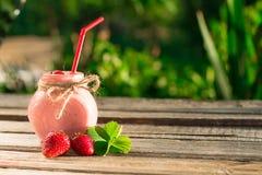 在玻璃瓶子的草莓圆滑的人,在木桌 免版税库存图片